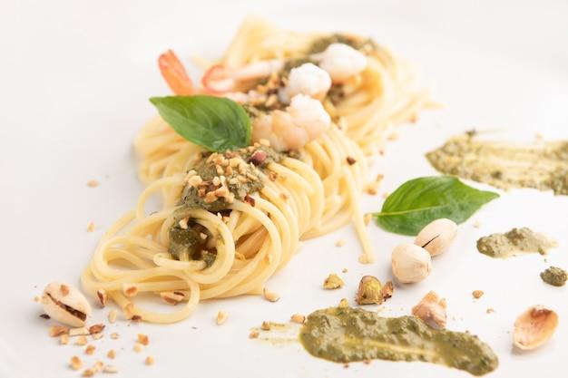 Espaguete isolado com camarão e pesto no branco