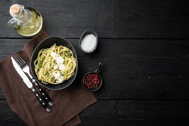Espaguete italiano com pesto de manjericão caseiro com parmigiano e queijo ricota, em uma tigela, na mesa de madeira preta