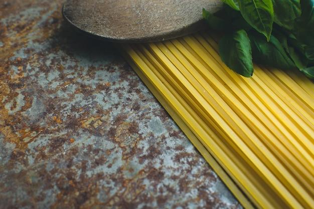 Espaguete macarrão com manjericão e colher de pau em um fundo metálico enferrujado