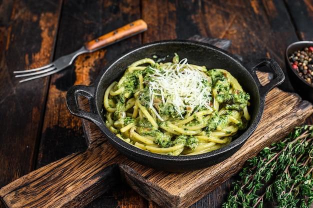 Espaguete macarrão com molho pesto, espinafre e parmesão em uma panela. fundo de madeira escuro. vista do topo.
