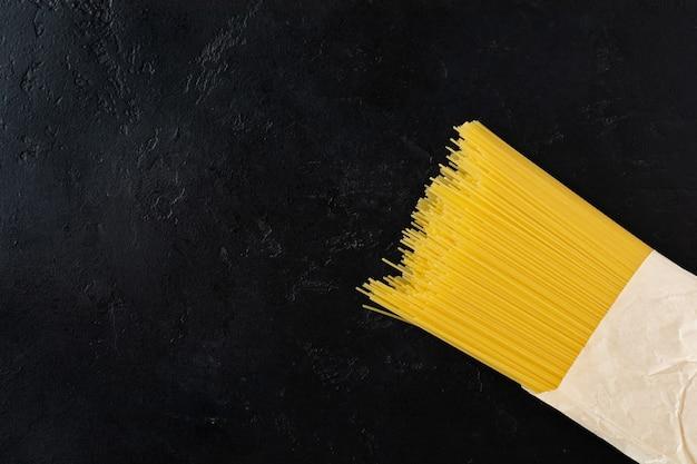 Espaguete macarrão cru em um saco de papel sobre uma mesa de concreto preto. conceito de cozinha. vista superior com espaço de cópia.