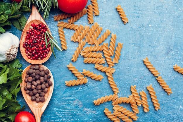 Espaguete macarrão, legumes e especiarias, na mesa de madeira