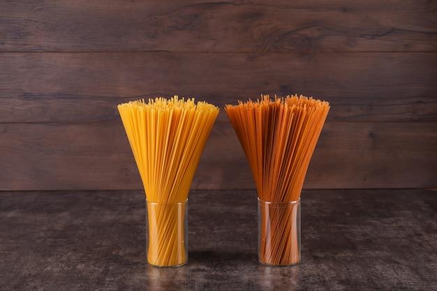 Espaguete marrom e amarelo em copos na superfície de madeira