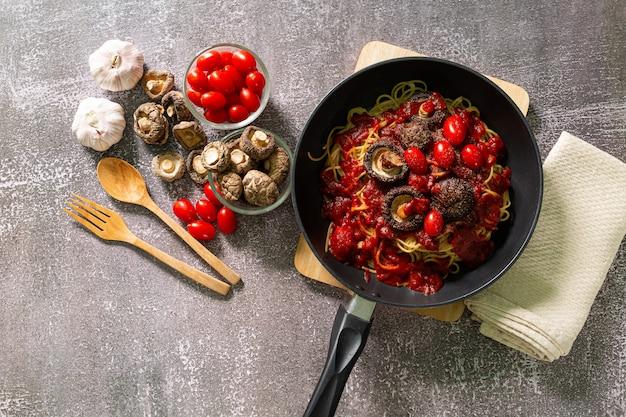 Espaguete na frigideira vista superior de uma deliciosa massa à bolonhesa na frigideira perto dos ingredientes
