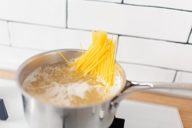 Espaguete na panela, cozinhar em água fervente em um fogão a gás. macarrão de milho sem glúten amarelo