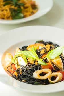 Espaguete negro com frutos do mar em chapa branca