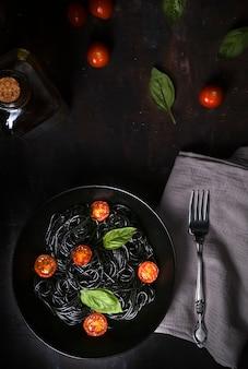 Espaguete preto com tomate cereja e manjericão