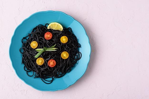 Espaguete preto de vista superior com tinta de choco com tomate cereja amarelo e vermelho em placa azul em fundo rosa com espaço de cópia, conceito de hora de comer