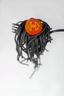 Espaguete preto no garfo com tomate no fundo claro macarrão preto com tomate