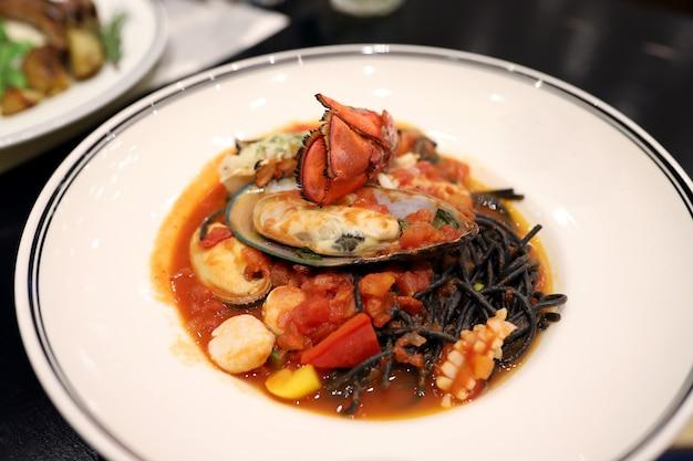 Espaguete preto refogue com frutos do mar, como lagosta, mexilhão, lula, vieiras em um prato branco do restaurante. preto vem da tinta da lula.