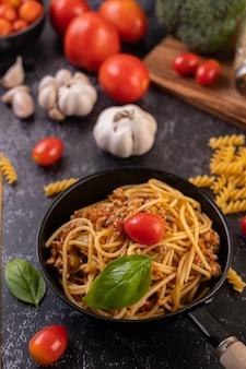 Espaguete refogado em uma frigideira frita com tomate e manjericão