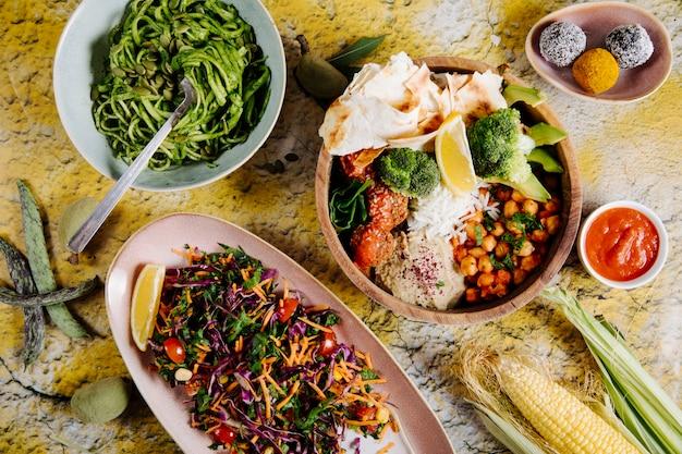 Espaguete, salada de legumes e prato principal, com legumes e biscoitos.