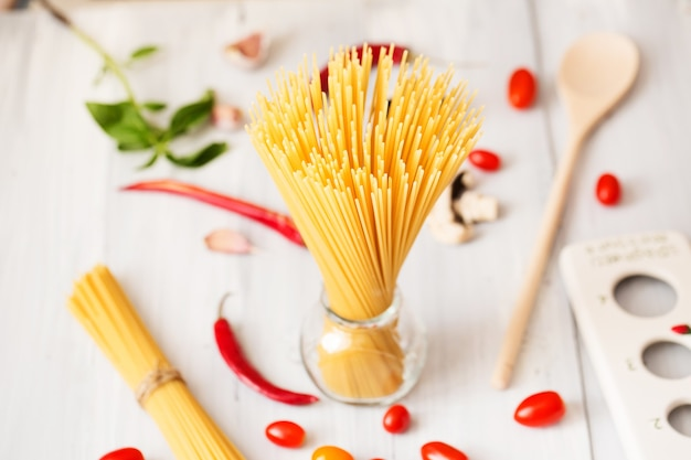 Espaguete seco italiano cru em pé sobre uma mesa de madeira.