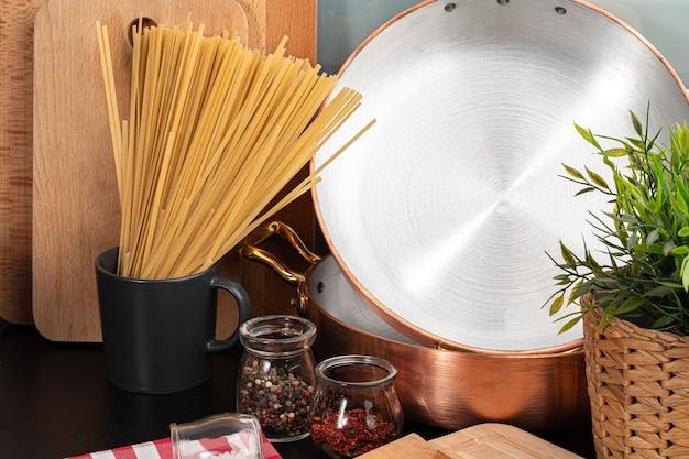 Espaguete seco na bancada da cozinha com utensílios de cozinha de perto