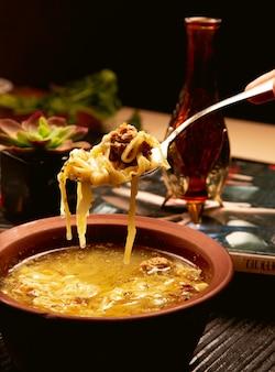 Espaguete, sopa de macarrão com almôndegas na tigela de cerâmica.