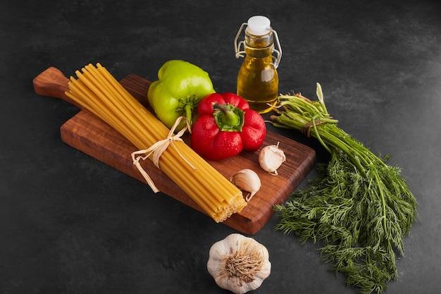Espaguetes com legumes ao redor.