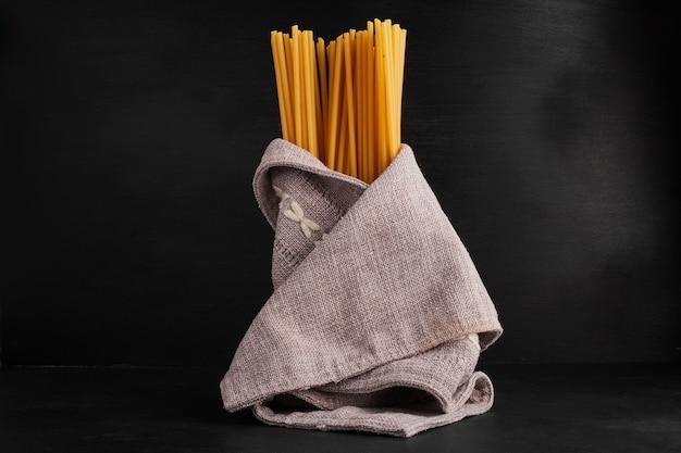 Espaguetes enrolados em um pano de prato.