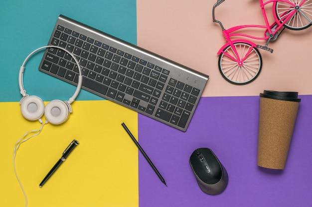 Espalhados em um teclado de mesa colorido, fones de ouvido e um brinquedo de bicicleta. local de trabalho do designer.