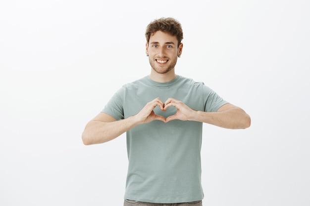 Espalhe o amor, não a guerra. retrato de um cara feliz de aparência amigável e positivo em brincos mostrando um gesto de coração sobre o peito e sorrindo amplamente enquanto expressa afeto ou emoções românticas sobre uma parede cinza