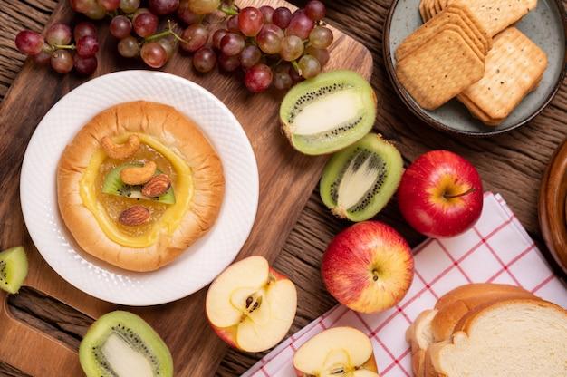 Espalhe o pão com geléia e coloque com kiwi e uvas