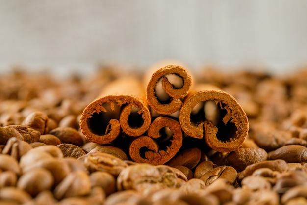 Espalhe sementes de café e paus de canela vista lateral