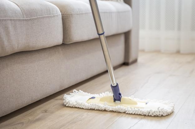 Espanador branco moderno, sendo usado para limpar um piso de madeira