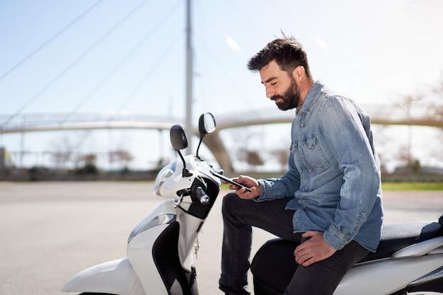 Espanhol jovem usando telefone celular ou smartphone sentado em sua scooter ao ar livre na cidade b.