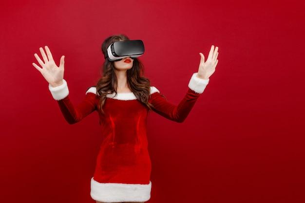Espantada com a jovem santa no vestido de natal, olhando no fone de ouvido, apontando as mãos de lado isoladas no vermelho w.