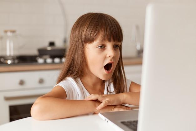 Espantada e espantada, criança do sexo feminino de cabelos escuros, sentada à mesa, olhando para a tela do laptop com a boca totalmente aberta, vê algo surpreendente, posando na cozinha.