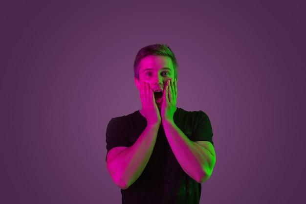 Espantado, chocado, questionado. retrato do homem caucasiano no fundo roxo do estúdio em luz de néon. lindo modelo masculino de camisa preta. conceito de emoções humanas, expressão facial, vendas, anúncio.