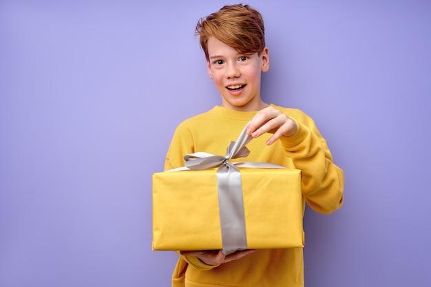 Espantado, curioso garotinho adorável, desempacotando a caixa de presente com uma expressão de espanto engraçada, criança caucasiana impaciente vestida de amarelo, surpresa de aniversário de desempacotamento. estúdio tiro fundo roxo.
