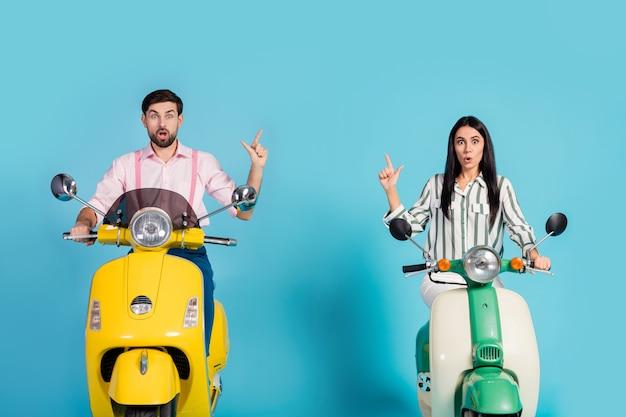 Espantado duas pessoas esposa marido motociclistas andar de bicicleta verde amarelo motorizada anúncios impressionados olhar no ponto de viagem dedo indicador copyspace vestir camisa rosa listrada parede cor azul isolada