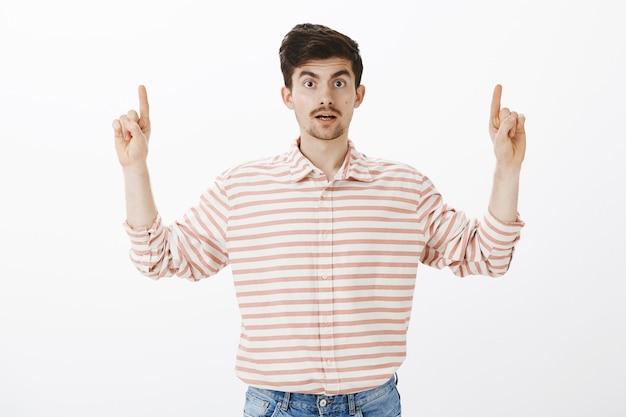 Espantado e intrigado homem barbudo caucasiano, levantando o dedo indicador e apontando para cima, dizendo uau, ficando chocado e surpreso ao ver um espaço de cópia interessante