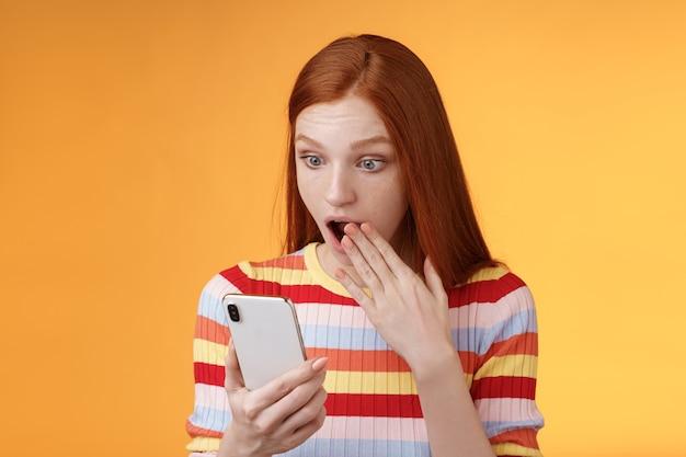 Espantado e mudo, jovem adolescente ruiva, menina, estudante, ofegante, mandíbula aberta, diga omg uau, boca, boca aberta, palma, olhar chocado, surpreso, tela do smartphone lendo fofocas frescas fundo laranja