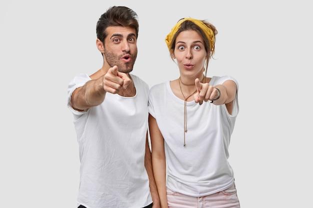 Espantado e surpreso com uma jovem e um homem vendo algo incrível, apontar diretamente com o dedo indicador, vestido com uma camiseta casual, isolado sobre a parede branca
