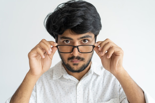 Espantado homem indiano inteligente, ajustando os óculos não acreditando em seus olhos.