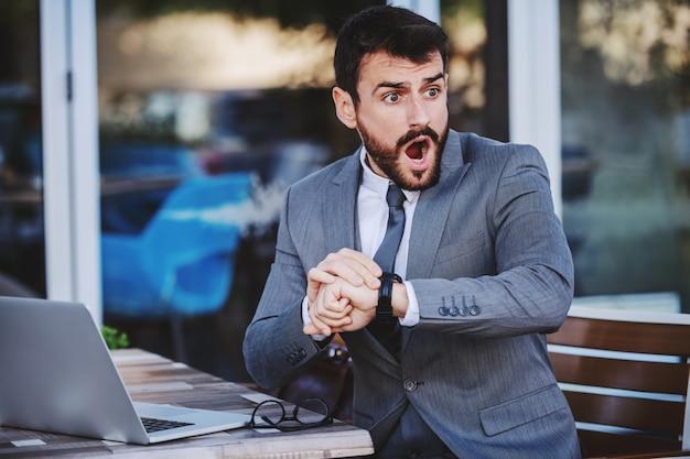 Espantado, jovem empresário barbudo caucasiano de terno percebendo que está atrasado para a reunião. exterior do café.