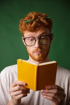 Espantado jovem estudante barbudo vermelho em copos lendo o caderno com caneta no cabelo