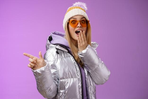 Espantado, mudo, surpreso, atraente namorada loira elegante de óculos escuros, jaqueta prateada brilhante chapéu de queixo caído impressionado arregalar os olhos chocados apontando para a esquerda atônito, fundo roxo.