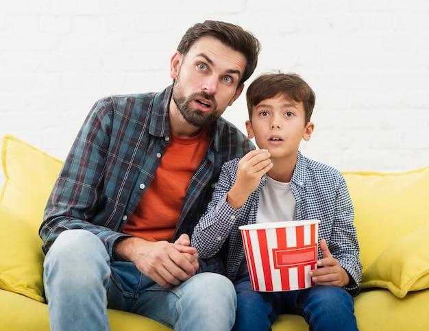 Espantado pai e filho assistindo tv