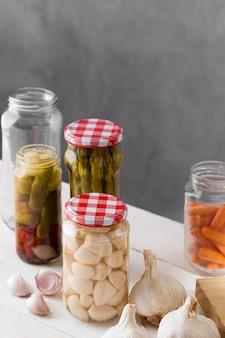 Espargos, alho e azeitonas conservados em potes de vidro