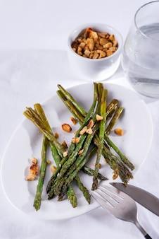 Espargos assados no azeite com nozes esmagadas e molho num prato branco. comida vegetariana.