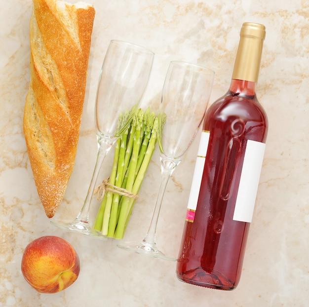 Espargos, baguete, pêssego e uma garrafa de vinho