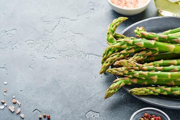 Espargos. bando de espargos verdes frescos pronto para cozinhar em fundo de mesa de pedra ardósia cinza. espaço da cópia da vista superior.