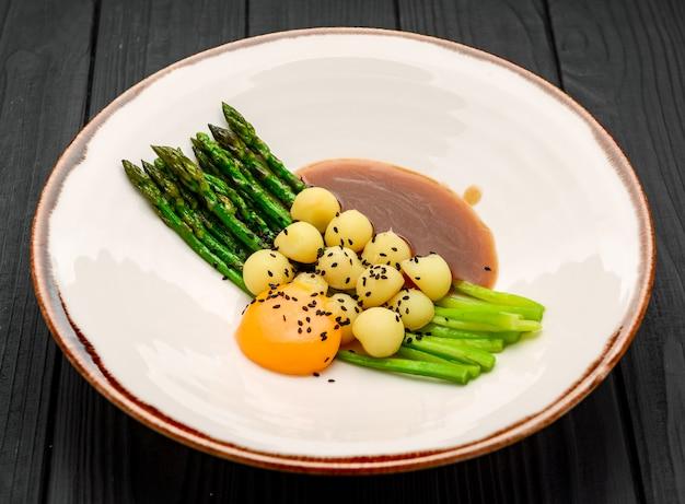 Espargos com batatas, com molho de carne e gema de ovo