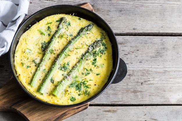 Espargos com ovos mexidos. omelete com aspargos em uma frigideira.