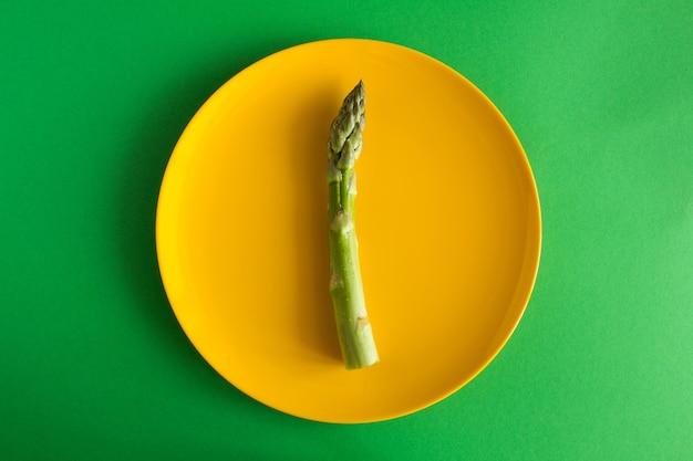 Espargos crus na placa amarela sobre o fundo verde. vista superior. conceito mínimo de dieta.