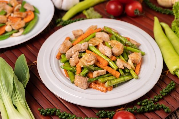 Espargos e cenouras salteados com carne de porco em um prato branco