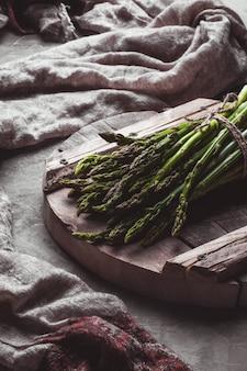 Espargos em uma placa de corte. alimentação saudável, saúde em um fundo de concreto.