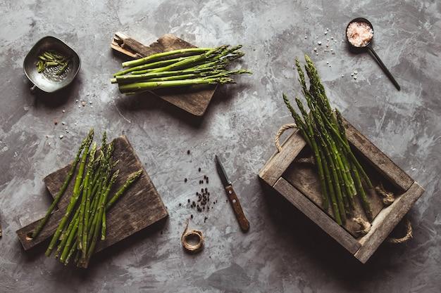 Espargos em uma placa de corte em uma caixa de madeira. alimentação saudável, saúde em um fundo de concreto.